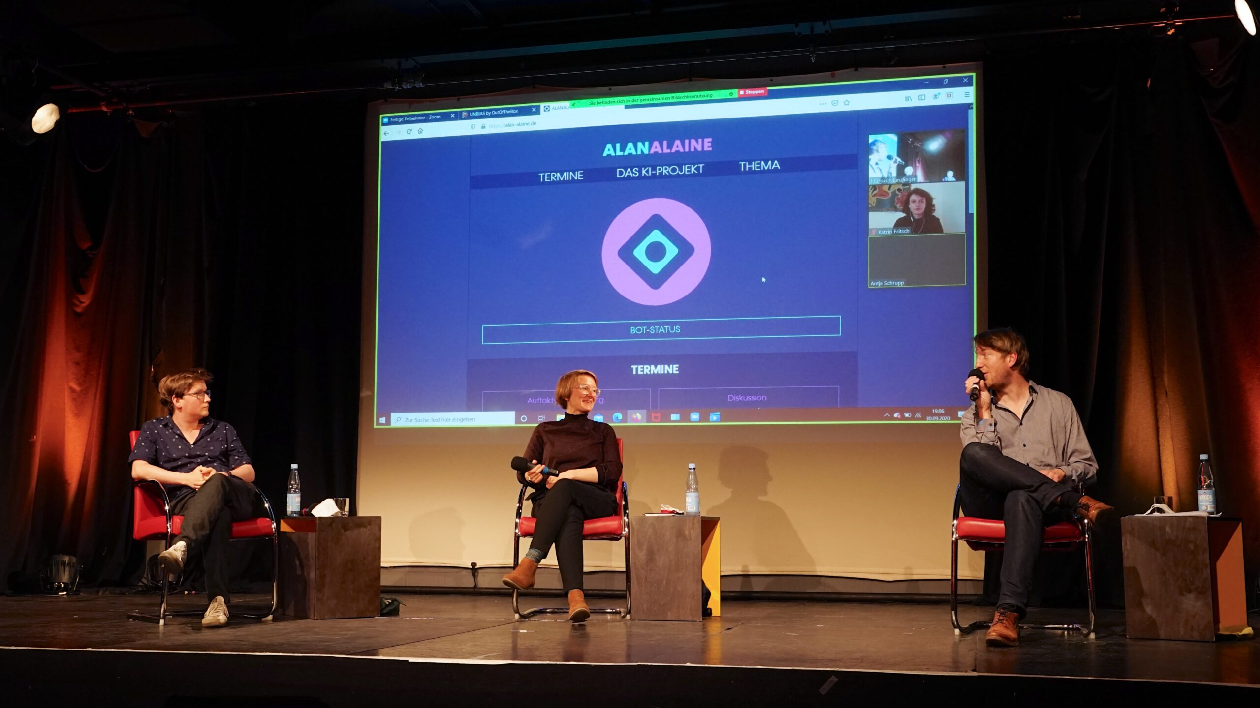 Foto der Bühne mit den drei Gesprächspartner:innen Susanne Schuster, Ricardo Gehn und Marcus Munzlinger.
